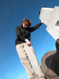 Rob leaning on a trig point